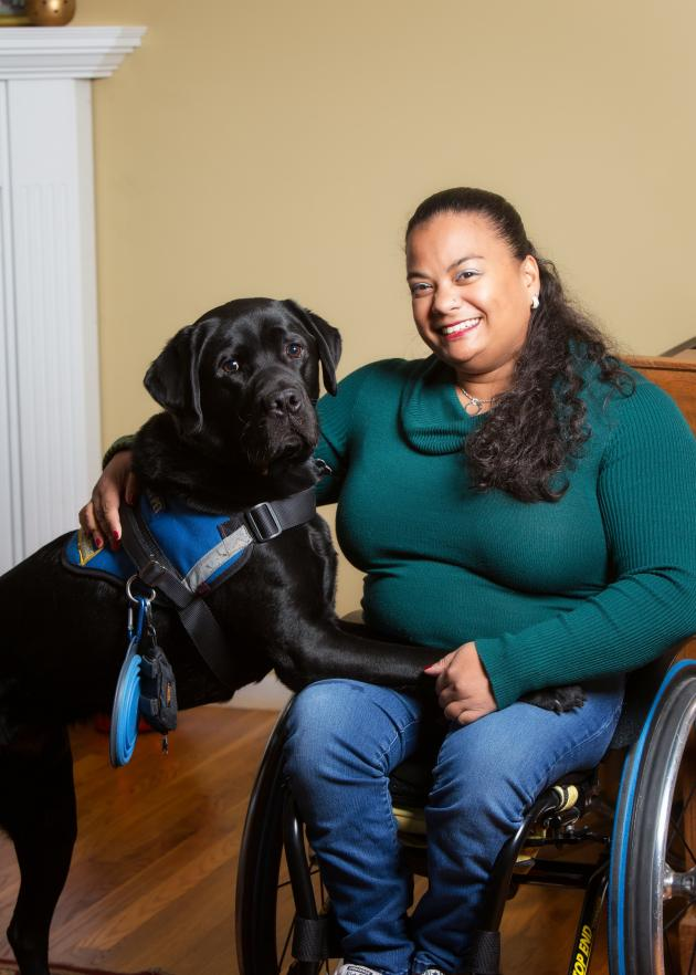 Photo of Anjali sitting in wheelchair with black service dog Kolton on lap.