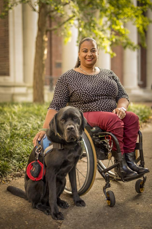 Photo of Anjali sitting in wheelchair with black service dog by side.